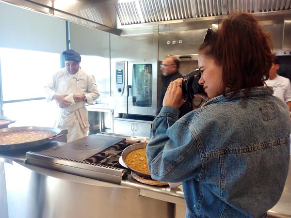 Alumna haciendo fotos mientras cocinan un arroz a banda en el CDT
