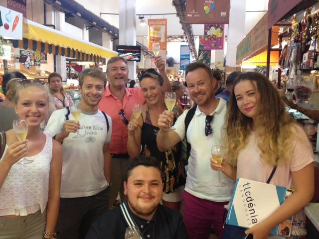 Estudiantes de español brindando en el mercado municipal en Denia