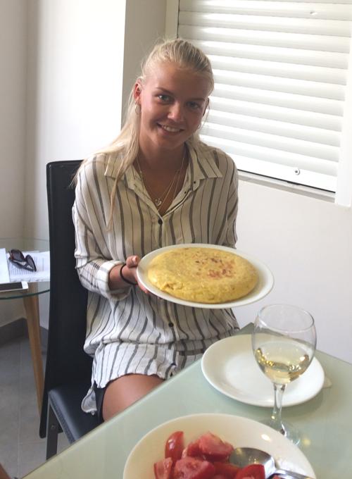 Alumna de español con la tortilla de patatas que cocinaron en el taller