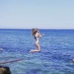 Student of Spanish jumping in the sea in Denia