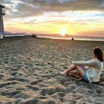 Student sitting on the beach in Denia in Spain