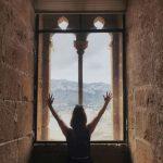 Chica mirando desde la ventana del castillo de Denia