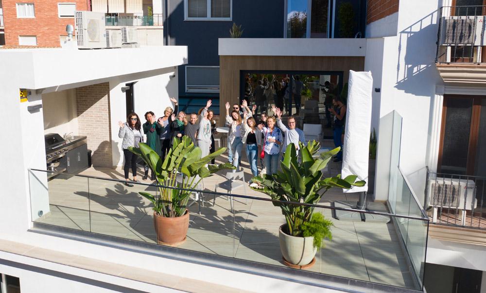 Estudiantes saludando en la terraza