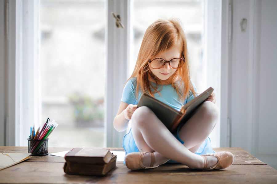 Niña con un libro estudiando inglés